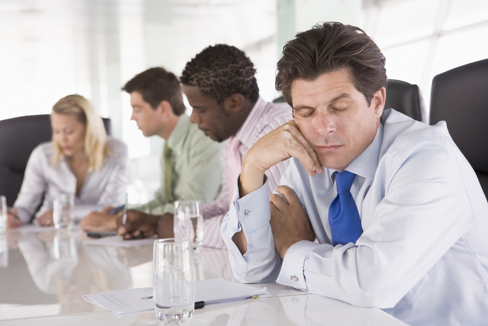 A man during a meeting wastes time by not paying attention.