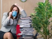 woman sitting next to a stack of paperwork
